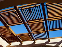 Modern design pergola arbor made wood and metal. With clear blue summer sky background Royalty Free Stock Image