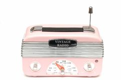 A modern design pink radio of the nostalgic era. A front facing photo taken on a modern design pink radio of the nostalgic era against a white backdrop royalty free stock photography