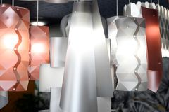 Modern design plastic chandeliers in close-up. Modern design plastic chandeliers of matte white and light red colors with glowing lamps, viewed in close-up royalty free stock images