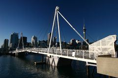 Skyline of Auckland CBD high-risers on shore and modern white Wynyard Crossing at Viaduct Harbor, Wynyard Quarter, New Zealand royalty free stock photo