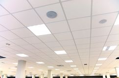White office ceiling with white tiles and lighting. Modern design white office ceiling with white tiles and lighting stock photo