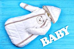 Modern design winter romper for newborn. Autumn or winter warm baby bodysuit on blue wooden background. Baby winter outdoor clothes Royalty Free Stock Photography