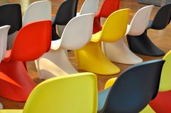 Colorful plastic chairs lined up in a room stock image