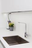 Modern designer chrome water tap over stainless steel kitchen sink. Interior of bright white kitchen. Stock Photo