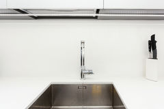 Modern designer chrome water tap over stainless steel kitchen sink. Interior of bright white kitchen. Royalty Free Stock Photography