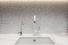 Modern designer chrome water tap over stainless steel kitchen sink. Interior of bright white kitchen. Water is poured through an open tap stock photo