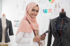 Modern designer sell product online. Muslim female designer using tablet pc to market and check his product online stock images