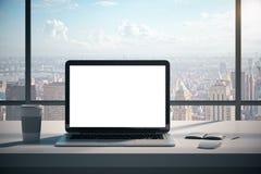Modern desk with empty white laptop stock photo