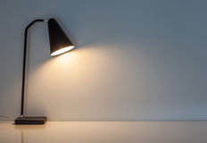 The modern desk lamp illuminate on the wall background. Royalty Free Stock Photography