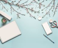 Modern desktop workplace flat lay with mock up of tablet computer and smart phone, cosmetic products, spring blossom. Branches , scissors, pen and green leaves stock photo