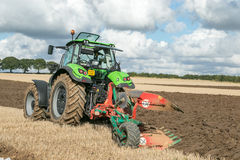 Modern deutz fahr tractor pulling a plough. Green modern deutz fahr tractor ploughing a field with plough working field at ploughing match sunroof open stock photos