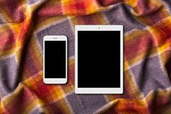 Modern devices on warm colorful coverlet: digital tablet and smart phone with blank screens. Domestic atmosphere. Unrecognizable p Stock Photo