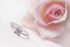 Modern diamond engagement ring. Close-up of diamond engagement ring with pink rose on background (shallow depth of field Royalty Free Stock Photo