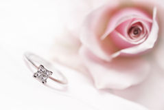 Modern diamond engagement ring. Close-up of diamond engagement ring with pink rose on background (shallow depth of field, bleached Stock Photos
