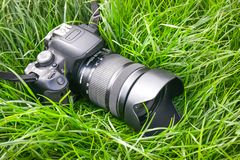 Modern digital camera in grass. Pause while photographing during travel. _ royalty free stock image