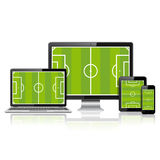 Modern digital devices with soccer field on screen Stock Photography