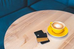 Modern digital gadget or smartphone with two plastic bank card lying on wooden table in cafe. High angle above top view or overhead, flat lay photo of cafe with stock images
