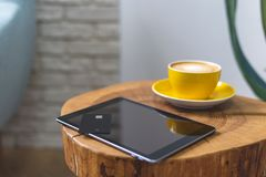 Modern digital gadgets with plastic card lying in cup of coffee on wooden table in cafe. High angle above top view.or overhead, flat lay photo. Modern digital stock photo
