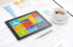 Modern digital tablet on office desk. Modern digital tablet with colorful modern user interface on a screen lying on a desk with some papers and documents, pen Royalty Free Stock Photo