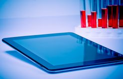 Modern digital tablet pc near test tube in laboratory Royalty Free Stock Photography