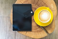 Modern digital tablet and plastic card lying on wooden table in cafe. Flat lay, flatlay view or overhead photo of modern digital tablet and plastic card lying on stock image