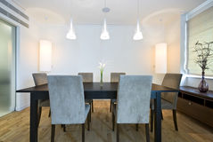 Modern dining area. With massive wooden table and six chairs Royalty Free Stock Photos