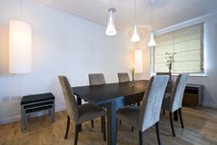 Modern dining area. With massive wooden table and six chairs Royalty Free Stock Photo
