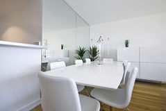 Modern dining area with massive white table. Beautiful white dining area with massive dining table and chairs for eight Stock Photography