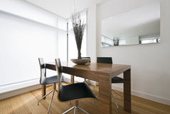 Modern dining area with wooden table stock image