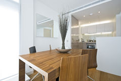 Modern dining area with wooden table. Designer chairs and kitchen in a backround Royalty Free Stock Photo