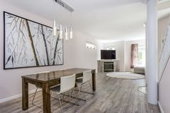 Modern dining area with a wooden table and leather chairs. Royalty Free Stock Photography
