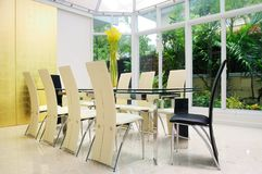 Modern dining room. Walls are decorated with gold with glass side walls to clear Royalty Free Stock Photo