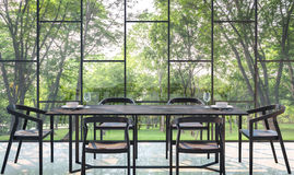 Modern dining room with garden view 3d rendering Image. There are large window overlooking the surrounding garden and nature and finished with black furniture Royalty Free Stock Photos