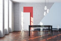 Gray and blue dining room. Modern dining room interior with gray and blue walls, a white and red door, a wooden floor and a black table with transparent chairs Royalty Free Stock Image