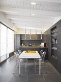 Modern dining room. Interior view of a modern dining room overlooking on the kitchen in the mansard Stock Photo