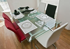 Modern dinning room. Modern expandable, glass table surrounded with beautiful leather chairs. Glassware and ceramics fits perfectly as decoration in this Royalty Free Stock Photography
