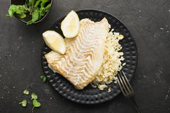 A modern dish is sea food. Fried cod white fish with rice on a side dish with slices of juicy lemon on a black plate and stock photography