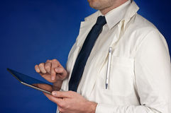 Modern doctor wearing tie with tablet  on blue Stock Photography