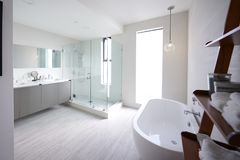 Modern domestic bathroom with shower cabin and freestanding bath, sunlight, no people royalty free stock photo