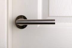 Modern door handle. On white wooden door Stock Photos