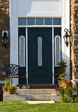 Modern Doorway. Elegant modern doorway of a stone house. A chair is on the left side of the door and potted plants and flowers are on either side Royalty Free Stock Image
