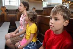 Modern, dottern och sonen sitter på bänk i kyrka Arkivbild