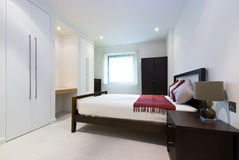 Modern double bedroom with king size bed. Built in wardrobes and bedside tables Stock Images