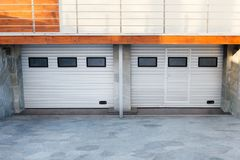 Modern double garage doors in a Luxury house. Modern double white garage doors in a Luxury house royalty free stock image