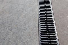 Modern drainagesysteem het afvoerkanaal op de weg of de stoep Stock Fotografie