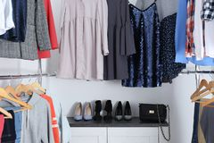 Modern dressing room with different stylish clothes. And shoes stock images