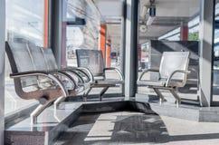 Modern drevstation som väntar Hall Metal Seats Sunny Day royaltyfri foto