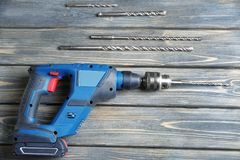 Modern drill with attachments on wooden table. In carpenter`s workshop Stock Photo