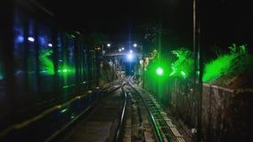 Modern driver-less metro train rush forward, along night Malaysia, Overground railway, bright road lights at night stock footage
