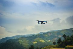 Modern Drone with camera flying on rice fields terraced at sunset in Mu Cang Chai, YenBai, Vietnam